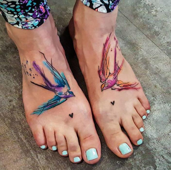 Tatuagem de pássaro em aquarela nos pés de uma mulher