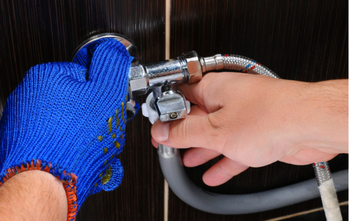 a furnace technician adjusting a drain hose