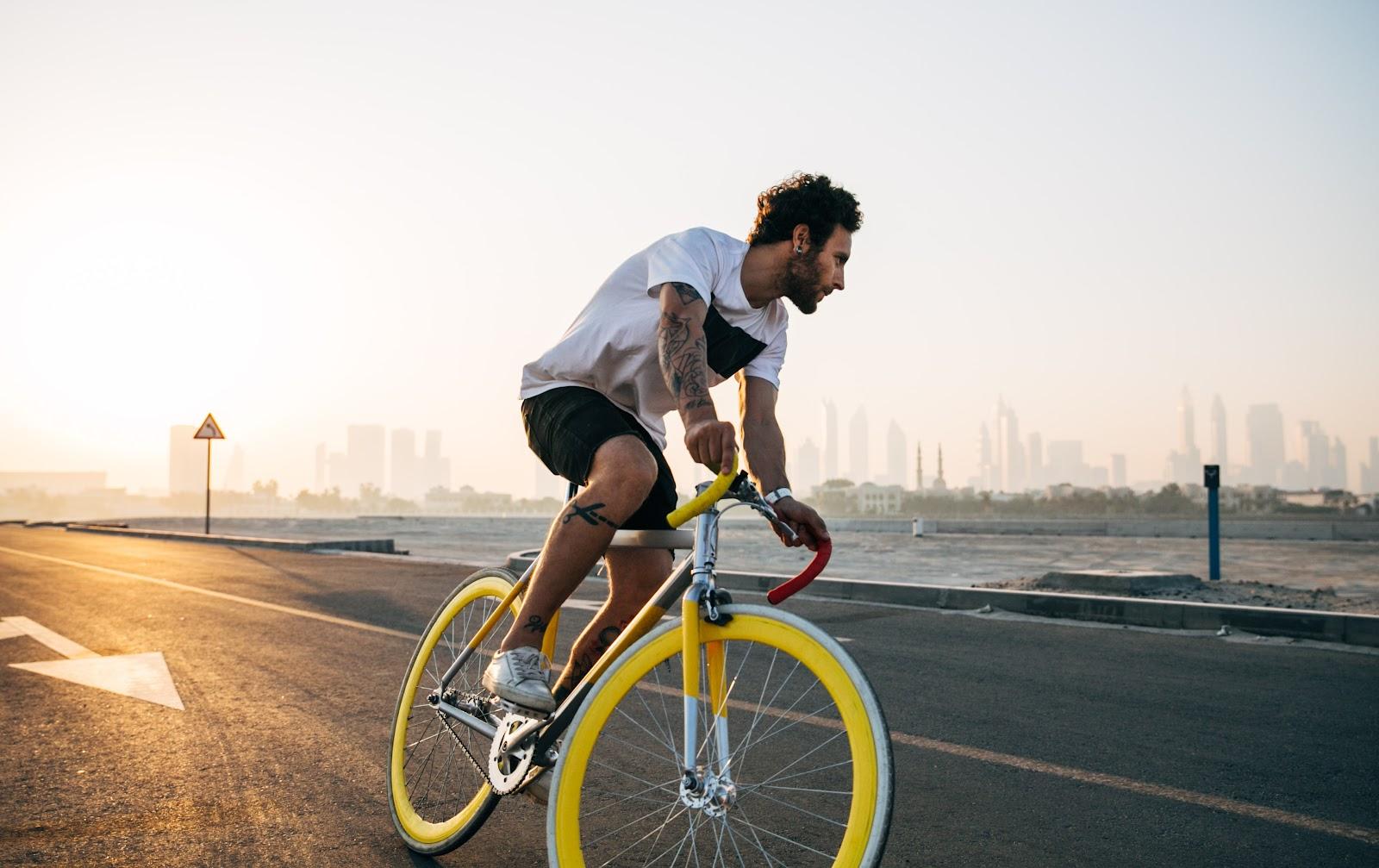 uomo in bici su lungomare che sterza per fare inversione su bici bianca con ruote gialle indirizzare l'attenzione