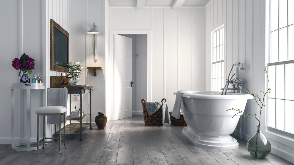 Elegant bathroom done up in whites with big windows letting in natural light