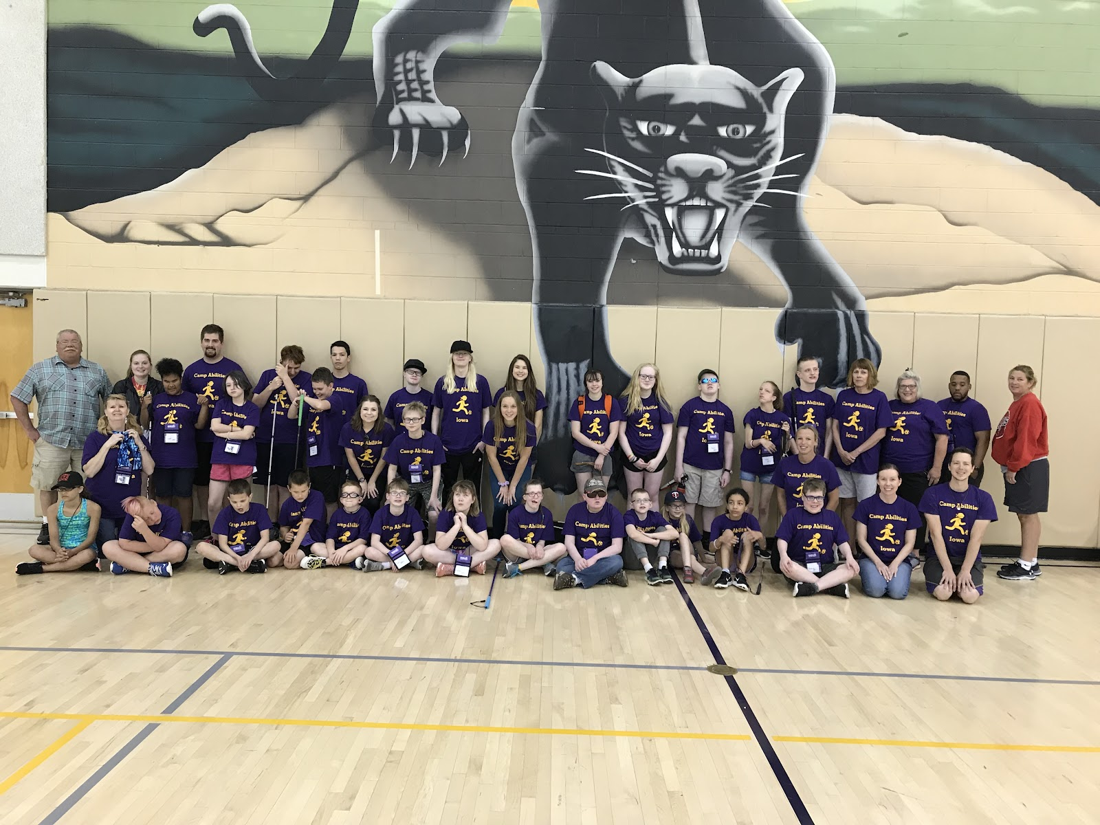 PD: Students and staff on gym floor in front of a mural of a panther at Univeristy of Northern Iowa  during 2019 Camp Abilities.