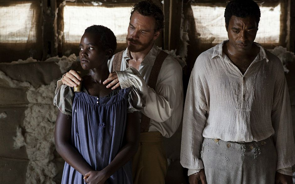 Cena de um homem segurando o ombro de uma mulher e outro homem, ao lado, em pé, com cabeça baixa.