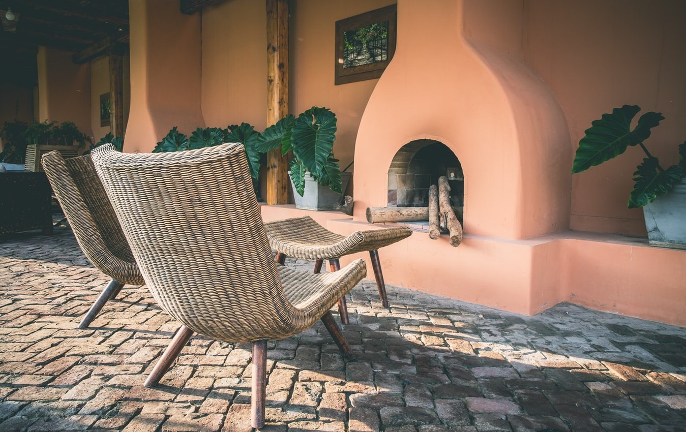 These wicker chairs next to an outdoor fire show off how important outdoor furniture is in any holiday rental
