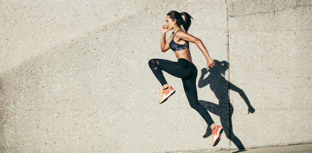 A woman in sports clothes exercising (running) outdoors near a concrete wall.
