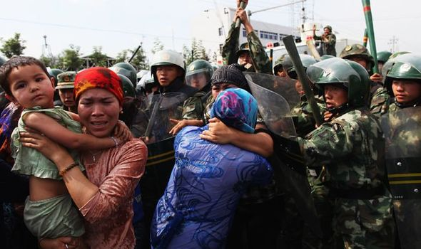 Chinese policemen push Uighur women who are protesting at a street on July 7, 2009 in Urumqi