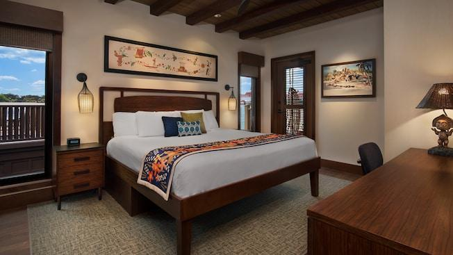 A bedroom featuring windows overlooking Walt Disney WorldResort, decorative pillows, lamps and a desk