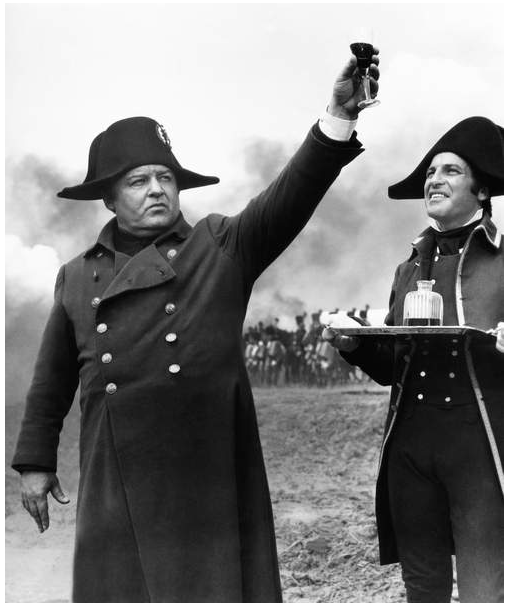 Image of a film still, Napoleon raises a glass, his general stares the glass with a smile. A sense of victory is present. Troops can be seen in the right background. The film was directed by directed by Sergey Bondarchuk in 1970 © Dino de Laurentiis Cinematografica/Mosfilm / Everett Collection / Bridgeman Images