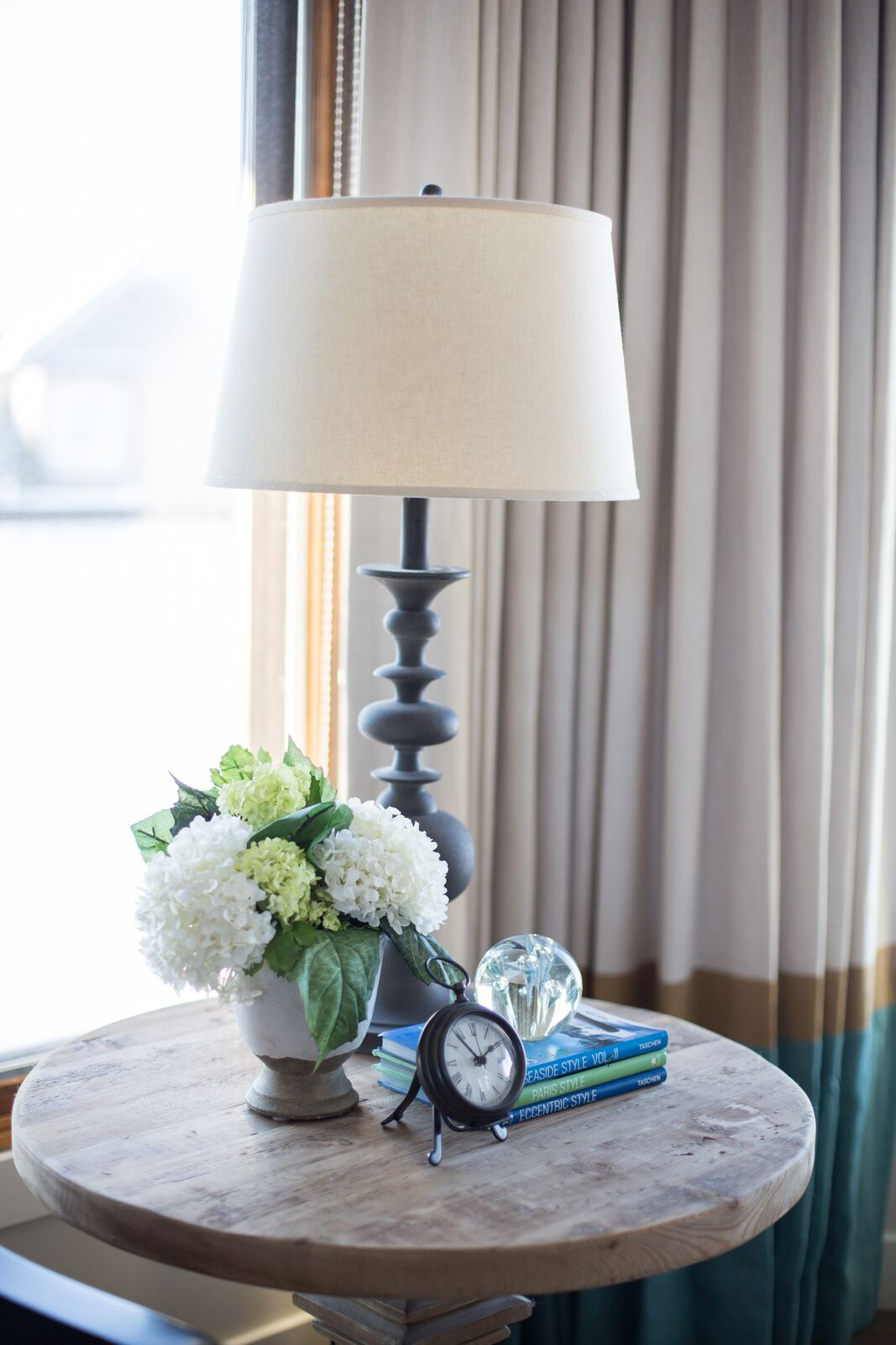 Vignette with clock, hydrangeas, traditional lamp, wood side table, blue and green books LeAnne Bunnell Interiors