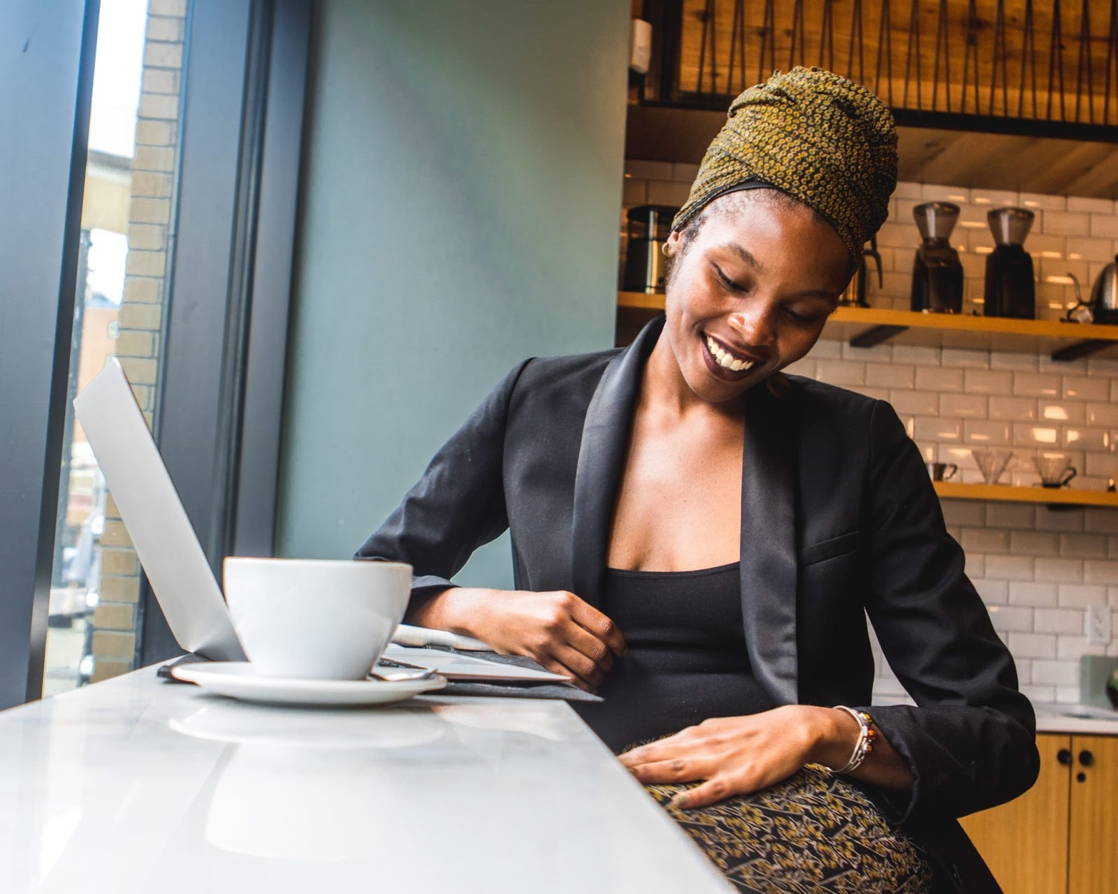 an Black woman sitting in a coffee shop and smiling