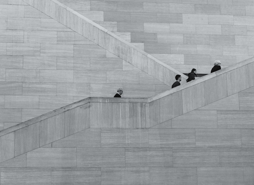 A black-and-white shot of people climbing up a tall concrete staircase