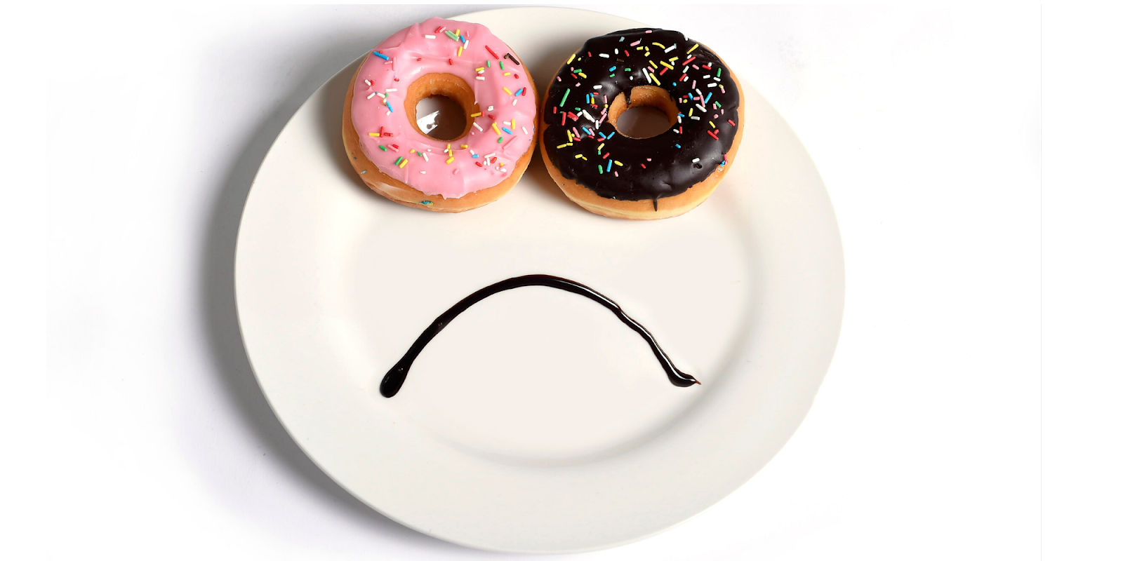 donut eyes and chocolate syrup frown on a plate making a sad face