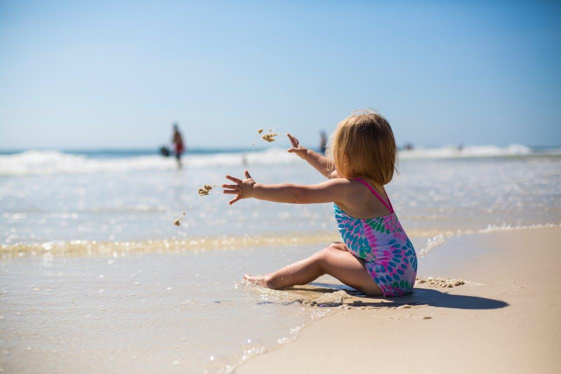 Малышка сидит на берегу днем