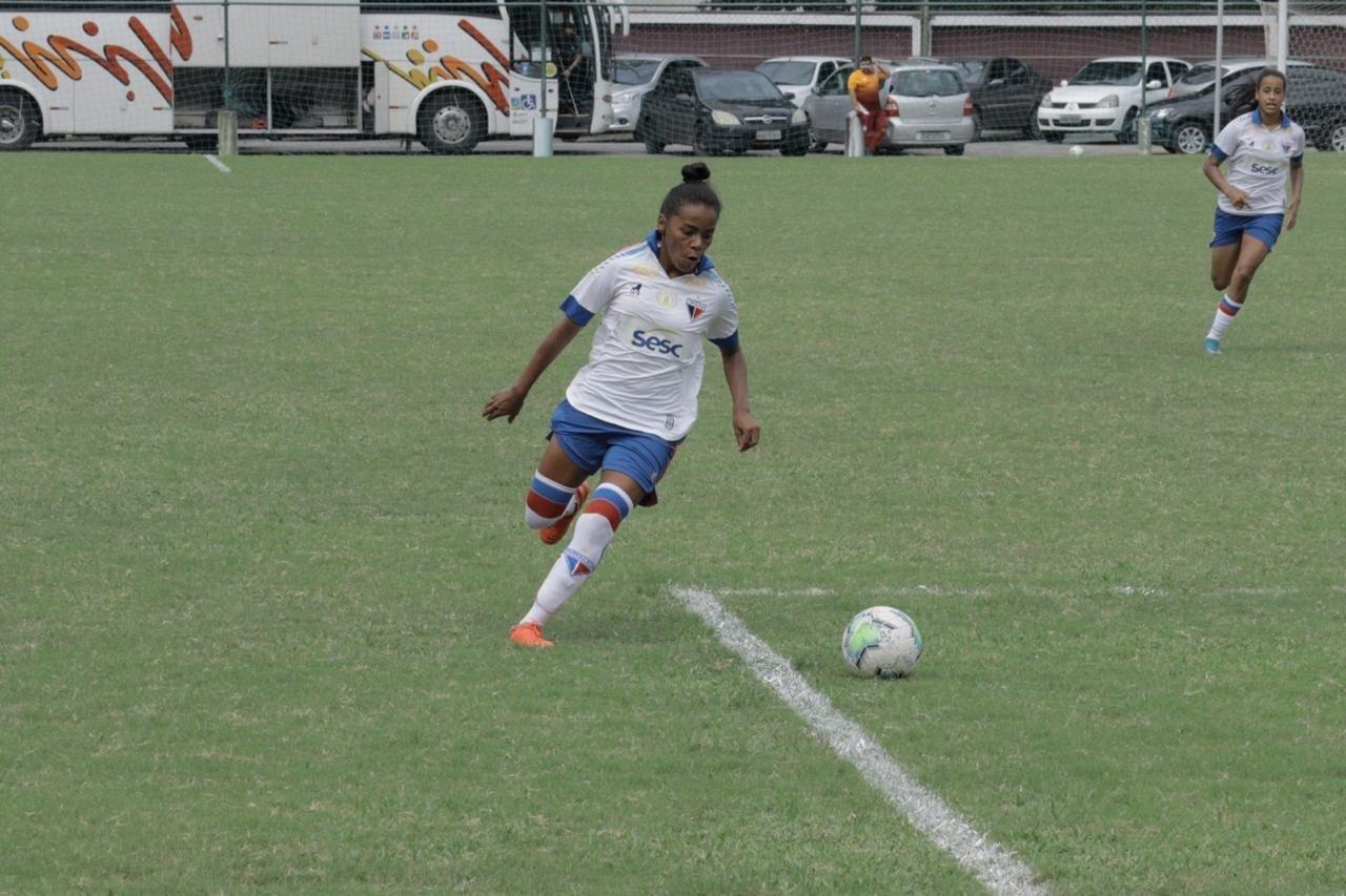 Mulher jogando futebol de campo  Descrição gerada automaticamente