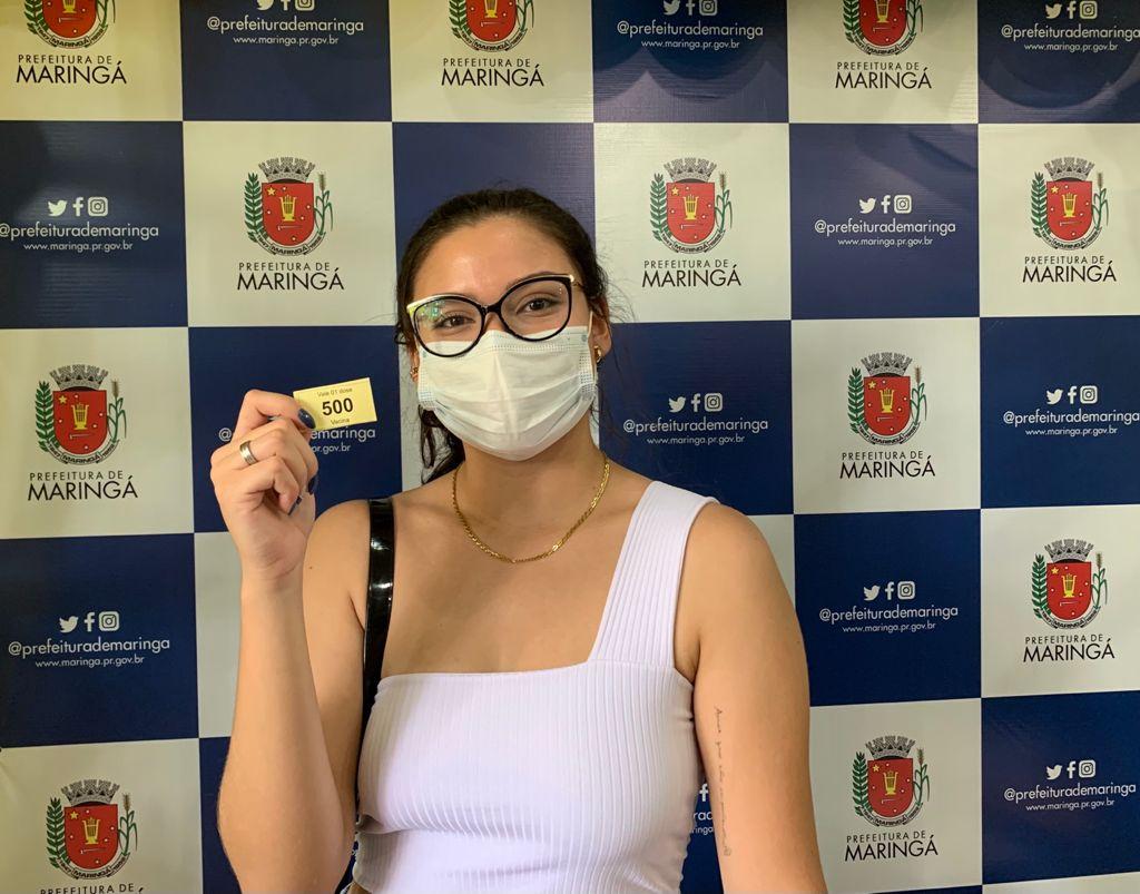 Mariane Vieira segura a senha número 500 após receber a vacina. Foto: Prefeitura de Maringá