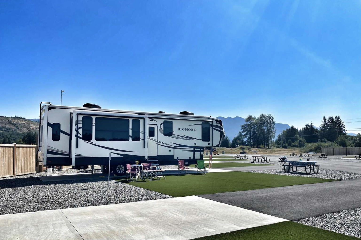RV parked at campground with chairs and picnic table with mountains in the background