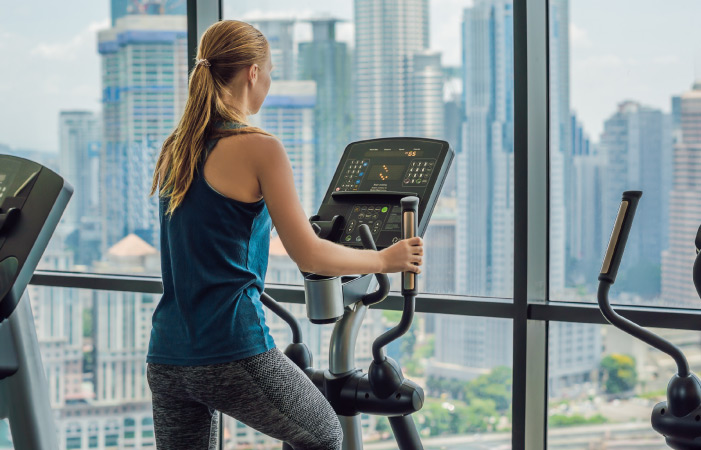 Woman exercising on an elliptical with a city view