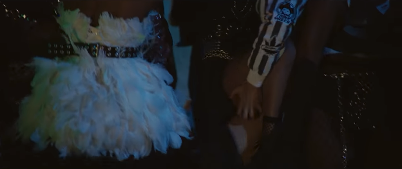 Black and brown bodies dancing at night. One person (Jane) wears a white feather dress.