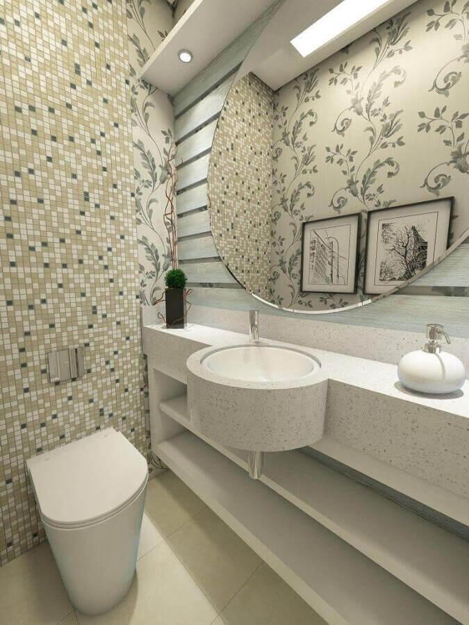 Lavabo com pia marmorizada, louças brancas, espelho redondo e pastilhas em tons neutros e parede de fundo com papel de parede floral.