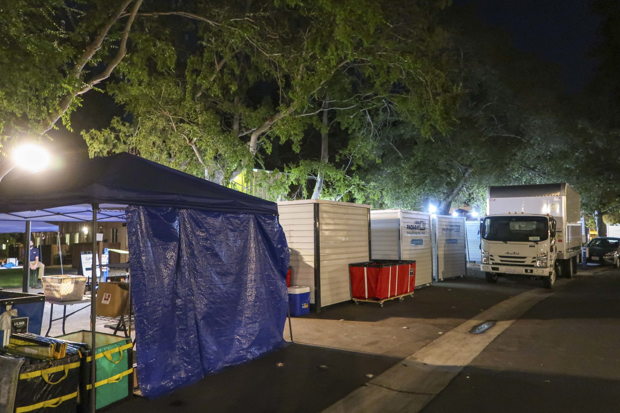 Tents and storage containers lining the streets next to residential buildings at night