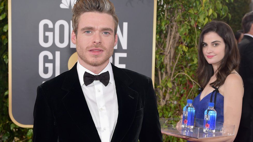 Buzz marketing example: actor Richard Madden is in a tuxedo at the Golden Globes. A lady holding a tray of Fiji Water appears in the background.