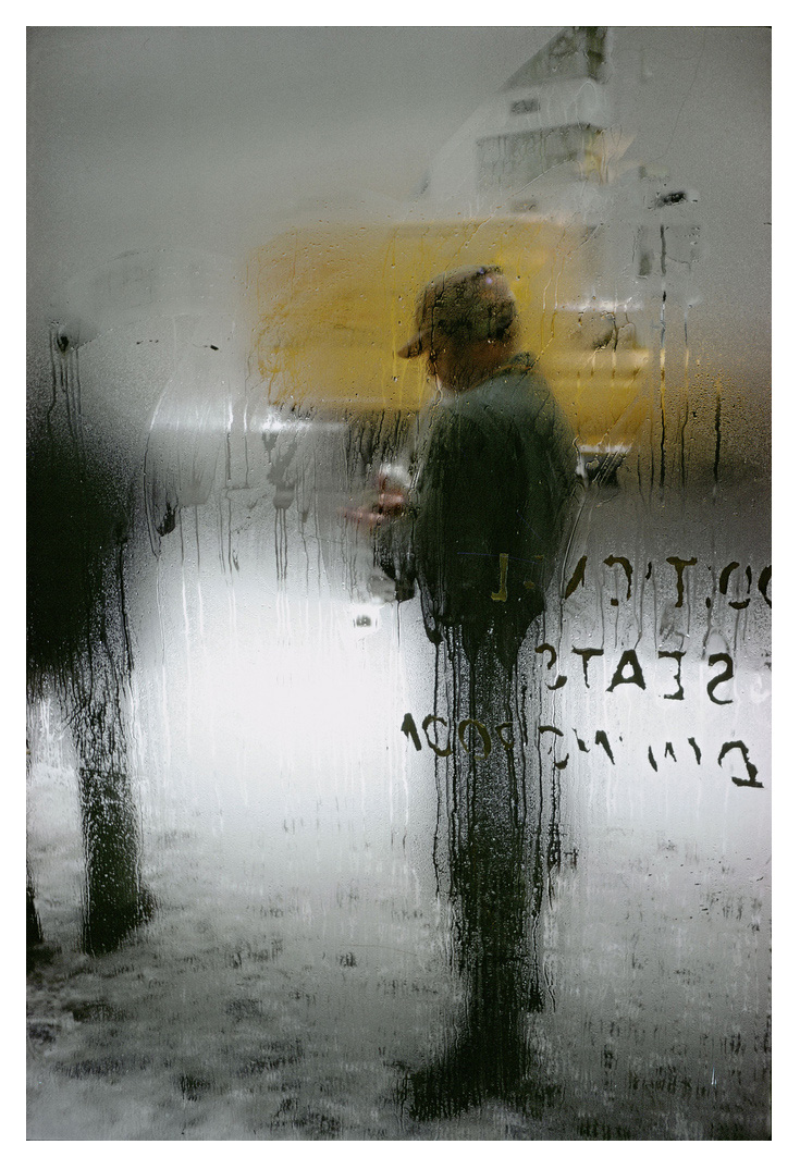 An image of a man stood in front of a steamy window by Saul Leiter