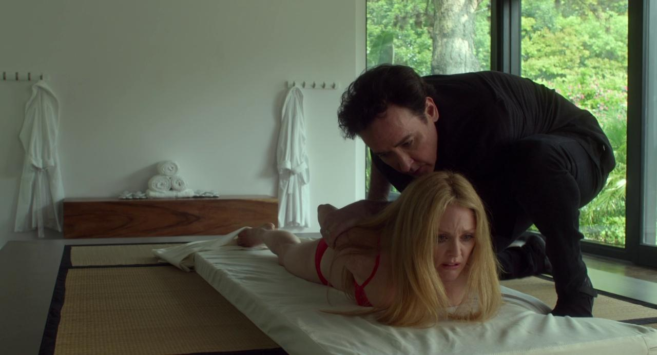 Julianne Moore as Havana in 'Maps to the Stars' (2014). Havana is in what looks like a therapeutic massage session, she is lying on a flat white bed in her underwear whilst a man dressed in black bends her arms back behind her.