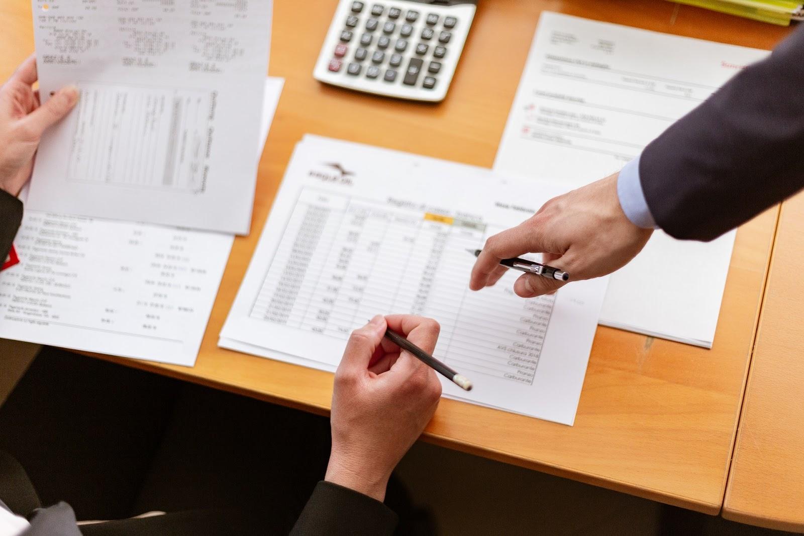Executivos verificando e assinando papéis
