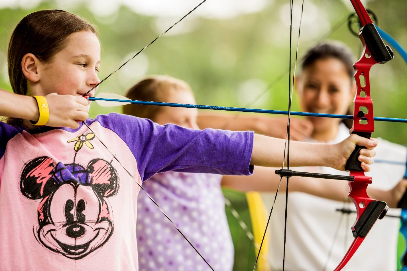 Young girl with Minnie Mouse on her shirt draws back an arrow during Disney archery.