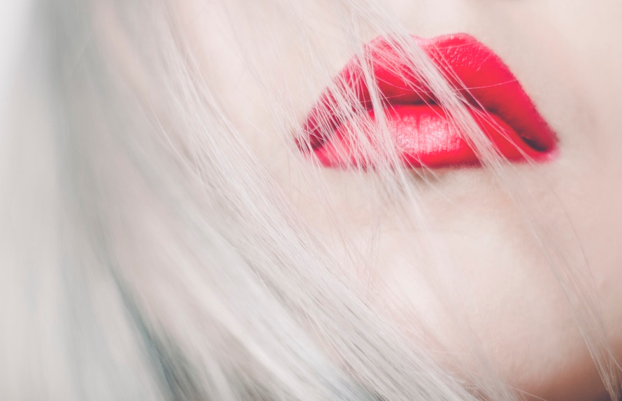 beauty tricks: red lipstick on blond young woman.