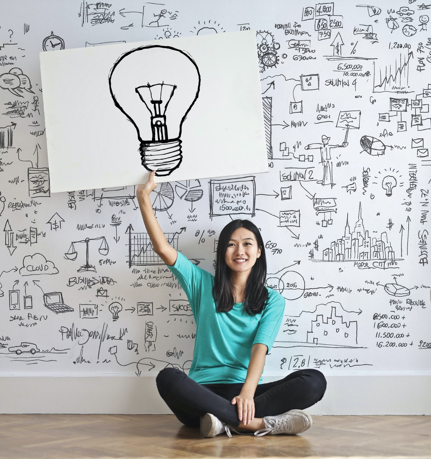 A smiling young woman holds a large poster with a light bulb on it. She is seated in front of a crowded vision board covered in ideas, topics, and how they all relate. Arrows, sketches, and words in black are visible on a white marker board.