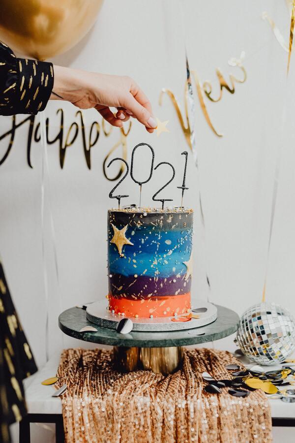 foto de um bolo colorido com velas numéricas formando 2021
