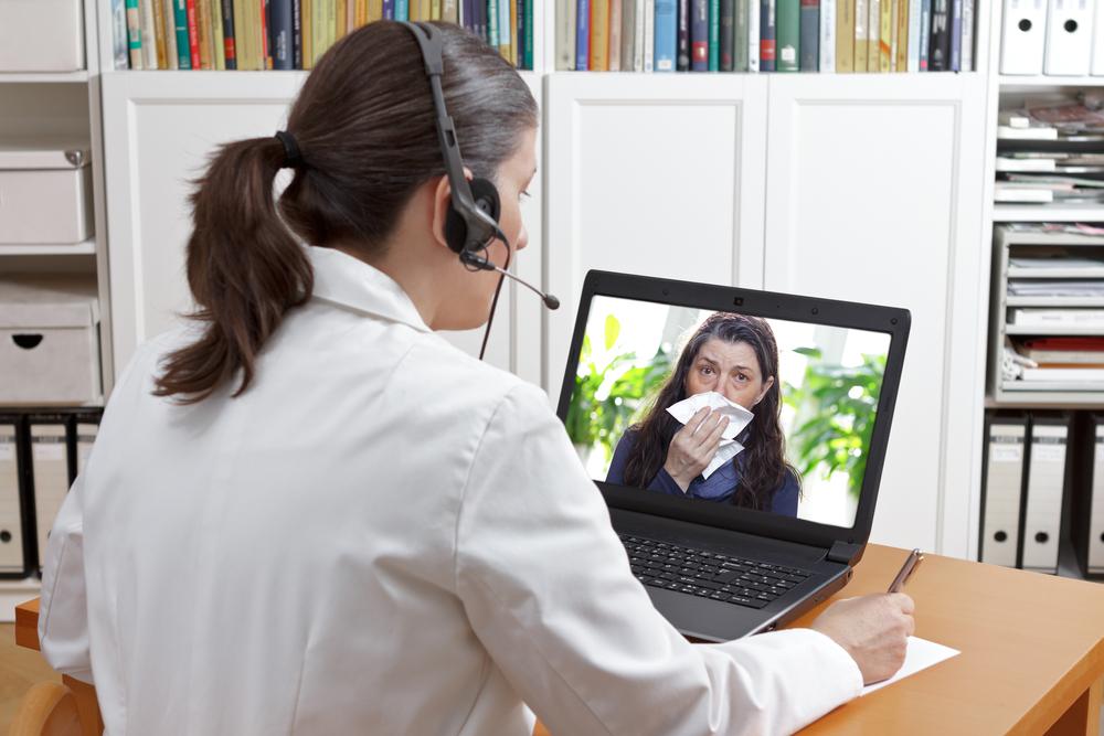 Médica atendendo paciente virtualmente com fones de ouvido e notebook