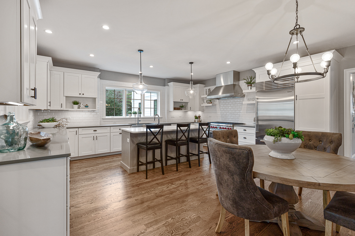Open floor plan, white kitchen and dining with wood floors, stainless appliances and blown glass pendant lighting.