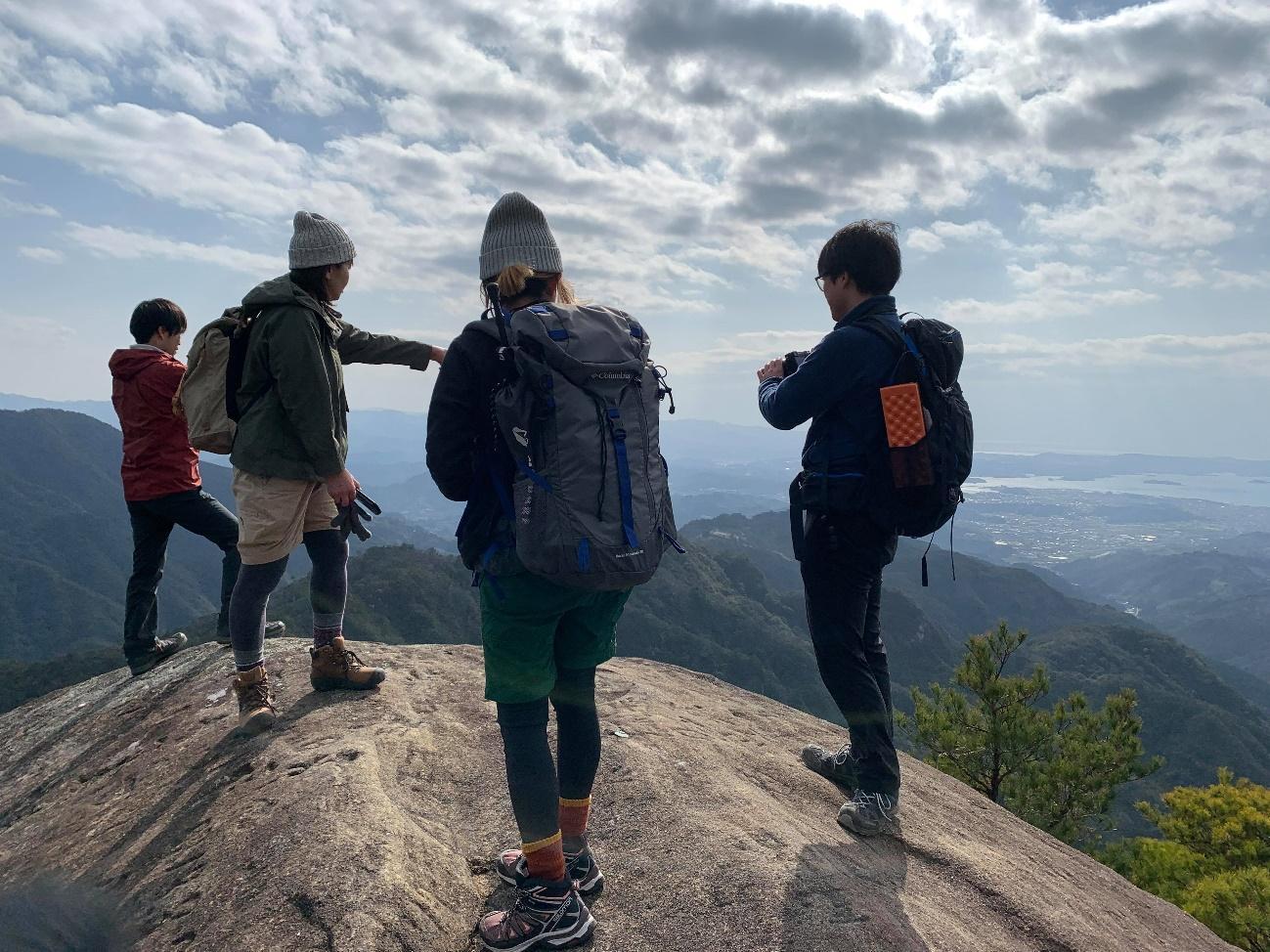 岩の上に立っている男性たち  中程度の精度で自動的に生成された説明