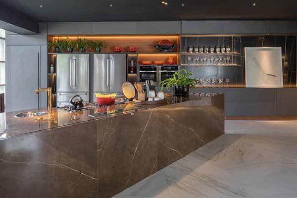 Cozinha com revestimento marmorizado no piso e bancada, paredes cinza com móvel planejado embutido e eletrodomésticos de inox