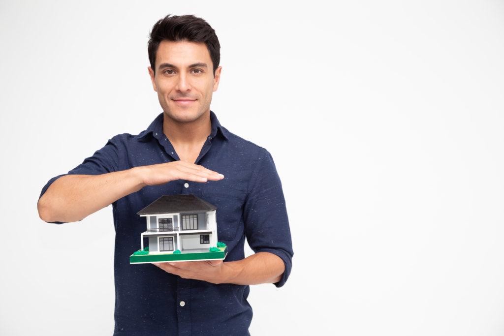 un homme avec une chemise bleue qui tient dans ses mains la maquette d'une maison de montréal