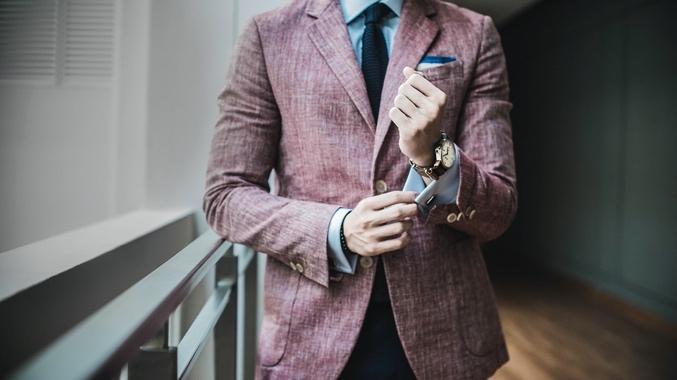 Das Bild zeigt einen Mann in einem leicht rötlichen Stoff Anzug. Es dient als Inspiration für das Hochzeitsoutfit, welches ein Mann trägt.