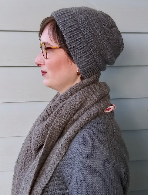 Siobhan stands in front of a weatherboard wall, wearing a grey handknit textured hat, similar style scarf, and plain grey handknit jumper. She is turned to the side to showcase the hat patterns..