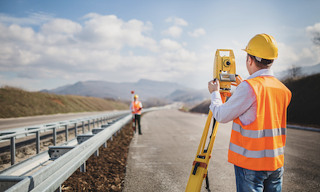 Picture of construction workers measuring something on the open road