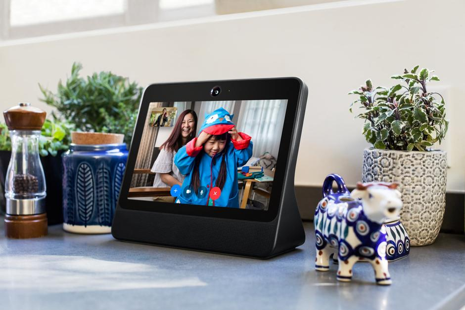 An image of Portal, a video call device that looks like a cross between an iPad and a picture frame, sitting on a desk inside of a home.