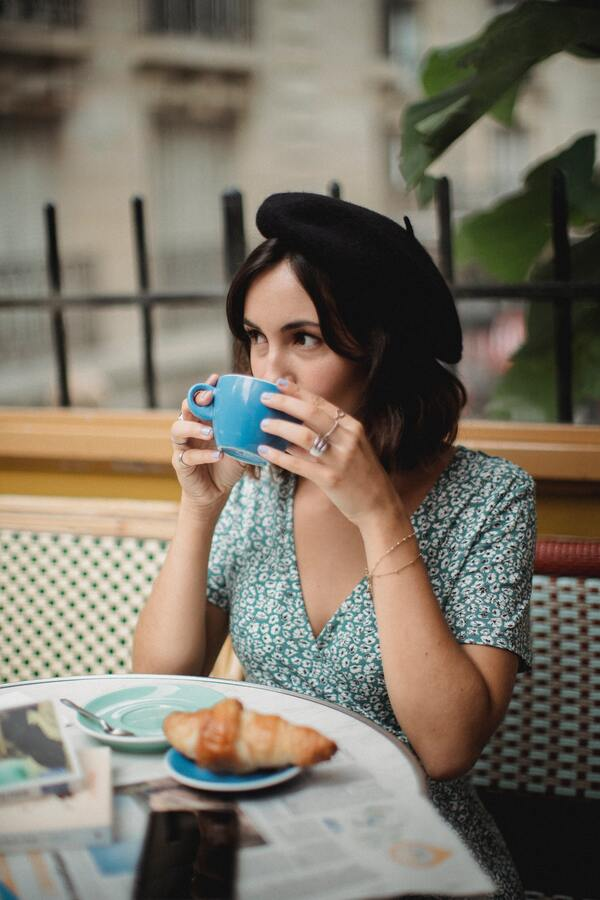 Uma mulher tomando um café em uma cafeteria e comendo um croissant de chocolate