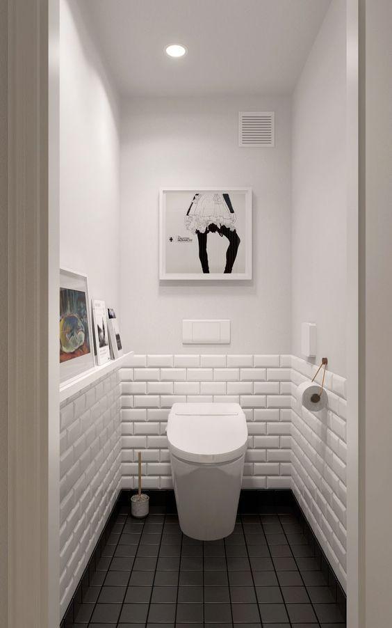 Banheiro com subway tiles branco em meia parede com uma pintura na cor branca acima, piso preto e quadros decorativos brancos.
