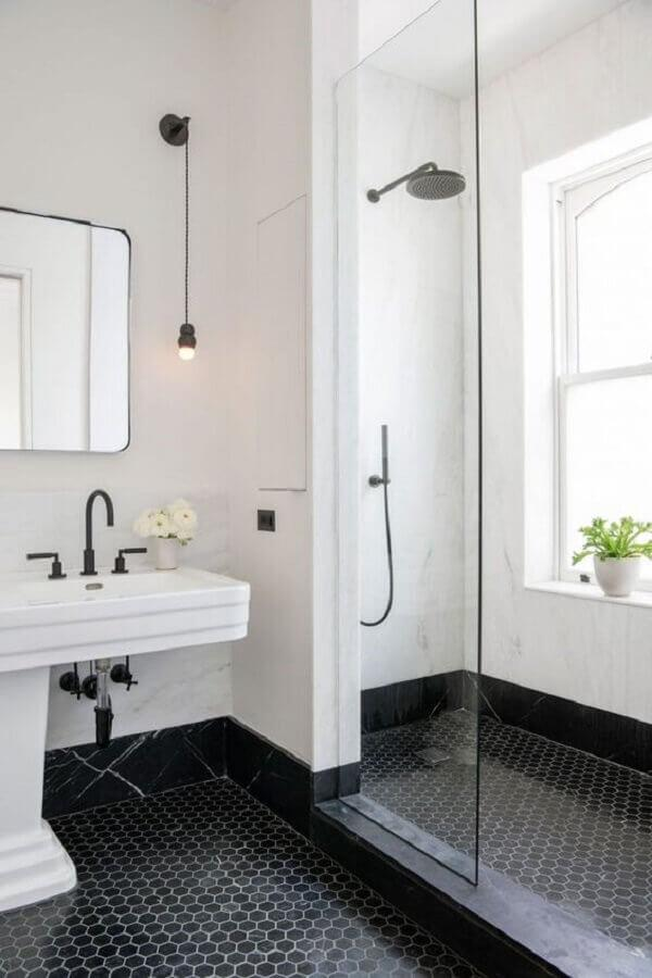Banheiro com piso hexagonal preto em formato pequeno, paredes pintadas de branco, pia branca, torneiras, chuveiro e luminárias pretas.