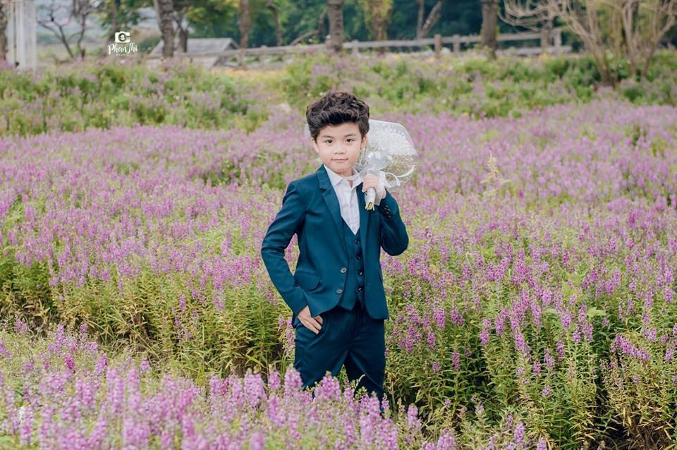 Trong hình ảnh có thể có: 1 người, đang đứng, hoa, trẻ em, ngoài trời và thiên nhiên