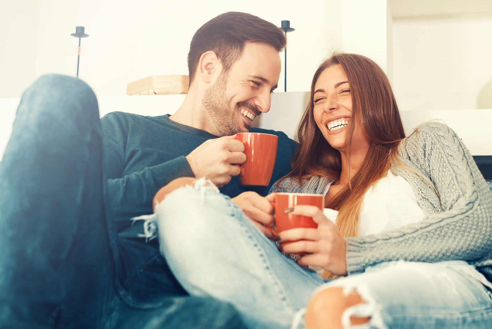 A couple sitting on a couch laughing together after setting marriage boundaries