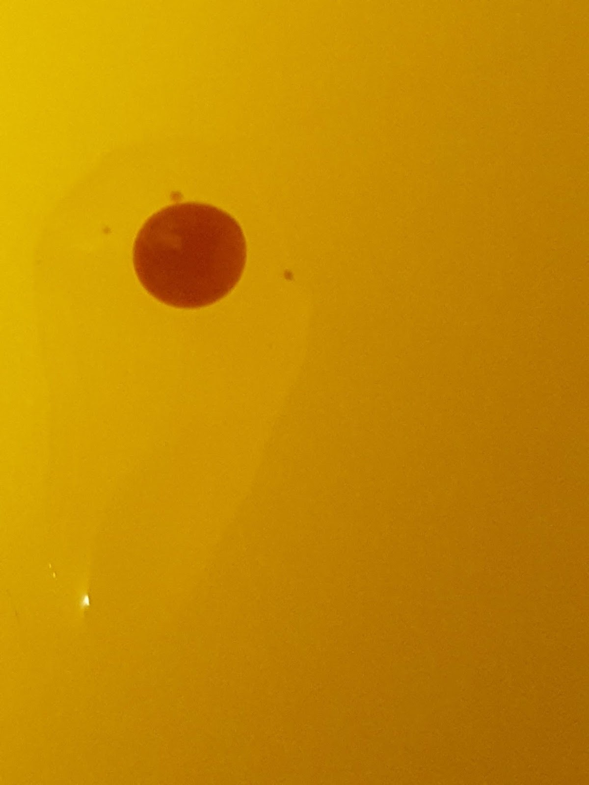 A brown drop is surrounded by a clear drop that is longer than it is wide. The background is yellow